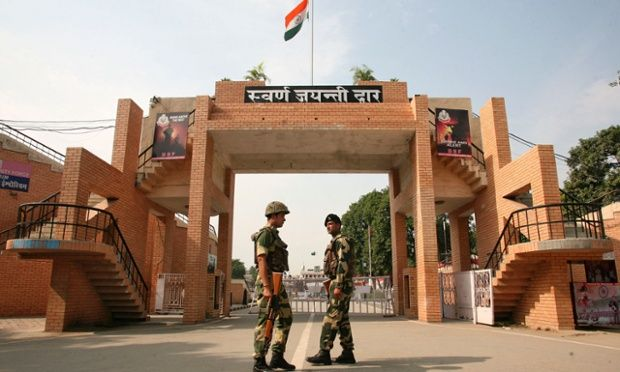 India's Border Security Force soldiers patrol in front of the golden jubilee gate at the Wagah border.