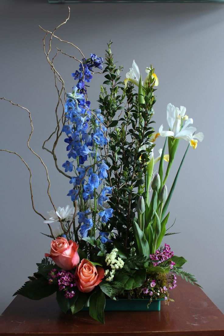 Garden style tabletop arrangement. (curly willow, delphiniums, myrtle, iris, roses, tulips, daisies, wax flower and statice)