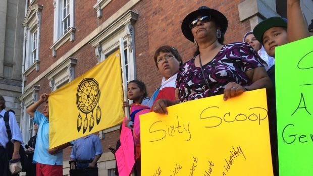Article: Supporters of the Sixties Scoop class-action lawsuit hold signs and flags outside a Toronto courthouse before lawyers press for a summary judgment on the case.
