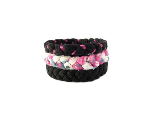 Three fabric bracelets made from recycled t shirts in black and colorful print. One bracelet is enriched by a fuchsia satin ribbon.