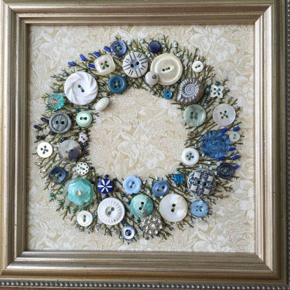 Handsewn framed picture of a wreath using blue & white buttons with embroidered leaves and stems. It takes me over 100 hours to hand sew all the buttons and attach all the seed beads to embelish this one of a kind miniture wreath. The fabric is then stretched to acid-free foamcore and framed in its 6.5 square frame. The back is covered and finished to hang on a wall or sit on a small easel. This is a one of a kind piece.