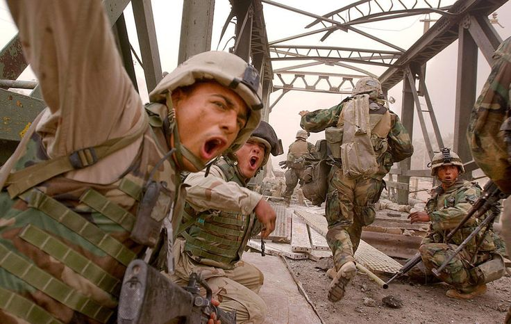U.S. Marines from the 3rd Batallion yell to urge infantrymen to rush across the damaged Baghdad Highway Bridge, Monday, April 7, 2003, as they moved forward into the city while under fire in the southeastern outskirts of Baghdad. (AP Photo/Boston Herald, Kuni Takahashi)