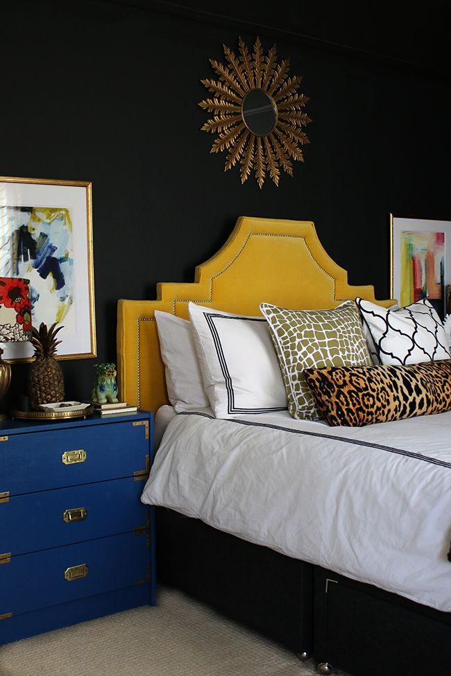 black bedroom with yellow velvet headboard, leopard print cushion, blue rast hack and colourful abstract art - see more on www.swoonworthy.co.uk