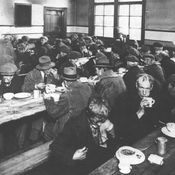In this picture, Men can be seen having breakfast in a building. This is a building that sets up food for people who are unemployed. At the time, since many people could not find work, they were left with no money to pay for food or shelter. Thus, having to resort to free food offered to survive.This source is very credible as it has been received from a very formal, edited and professional Canadian history website (http://www.thecanadianencyclopedia.ca).