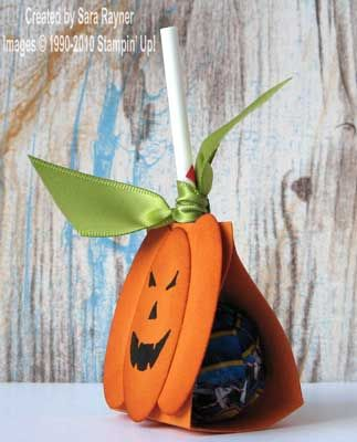 12cm x 3.5cm of Pumpkin Pie card, scored at 4.5cm and 7.5cm along the long edge.  fold around the lollipop and secure with a glue dot.on each side of lollipop.large oval punch for pumpkins.cajun craze ink sponged and old olive satin ribbon tied on.