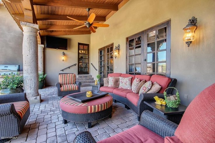 Southwestern Porch with Columns, Wall sconce, Brick floors, Exposed beam, French doors, Ceiling fan, High ceiling