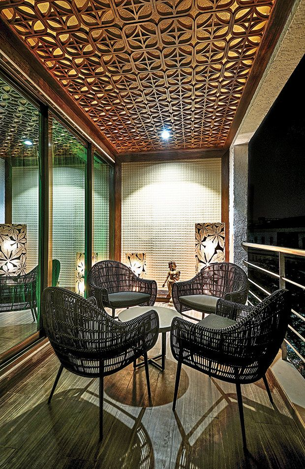 The outdoor deck, a warm and informal extension of the living area, has tobacco brown Italian marble flooring, a back-lit wooden trellis on the ceiling, sculptural wall with a tough bumpy texture and Indonesian rattan furniture.