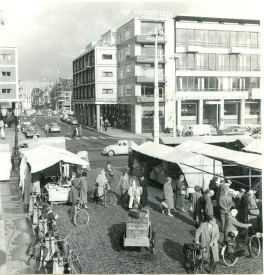 Groningen<br />De stad Groningen: De Grote Markt in 1960 met inkijk in de Oude Ebbingestraat. Op het gebouw op de hoek is een lichtreclame voor Barbarossa pils te zien en daarnaast het gebouw van de Amsterdamsche bank