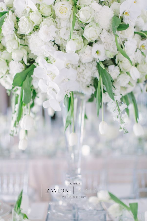 White wedding flowers in huge arrangements, crisp white and green wedding. Banquet tables with floral runners, elegant wedding. Luxury wedding.