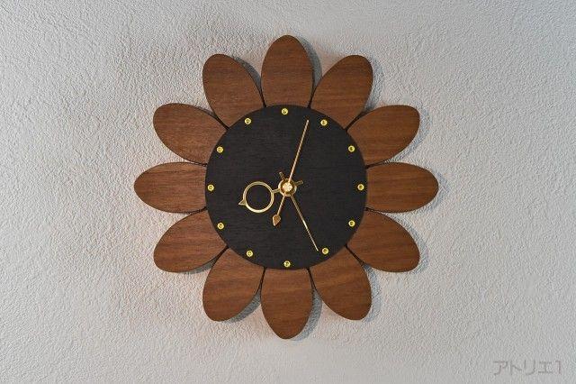 お部屋を元気に明るくするインテリア掛け時計です。見る人を元気にする青空に向かって高く伸びた先で夏の太陽の光を受けて咲くひまわりをぬくもりのある木で作った掛け時計です。 まわりの花びらの部分は、アフロルモシアというアフリカのコートジボワールに生育するマメ科の木で製作しました。インテリ掛け時計としての質感のバランスを考慮して、中心部はウエンジの木を使用しています。そして、ひまわりの管状花をスワロフスキーのシトリンを使用して表現して、時刻の目盛りにしました。アフロルモシアとウエンジの木は蜜蝋クリームで仕上げ、インテリア掛け時計としての質感とひまわりとしての花らしさのバランスがとれたお洒落な時計です。 ムーブメントは、カチコチ音のしないクオーツ時計のスイープを使用しているので、寝室の時計にもご利用できます。また、壁に取り付ける際に使用するフックなども背面板に当たらないように取り付け金具周辺も彫り込んであります。壁へのあたり部分は、壁を保護するようにフェルト仕上げになっています。ムーブメントの上部に彫り込みがあるのは、取り付けのフックがひっかからないようにとの配慮から加工しています。…