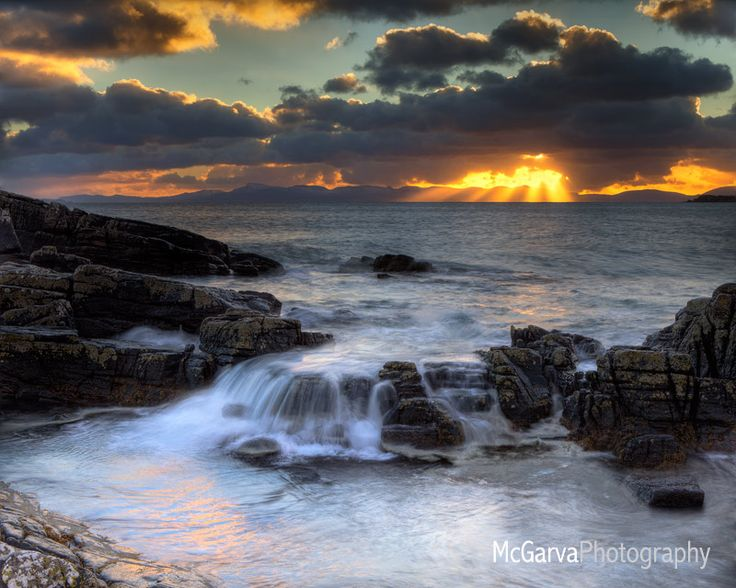 At an area on the Scottish west coast referred to locally as Big Sands near the town of Gairloch .... The rising tide created a wonderful waterfall waterfall effect on the foreground stones .... As the sun set moodily over the mountainous skyline of the Isle of Skye in the background