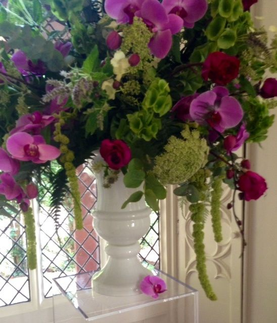 Lime green and pink flowers in a white urn
