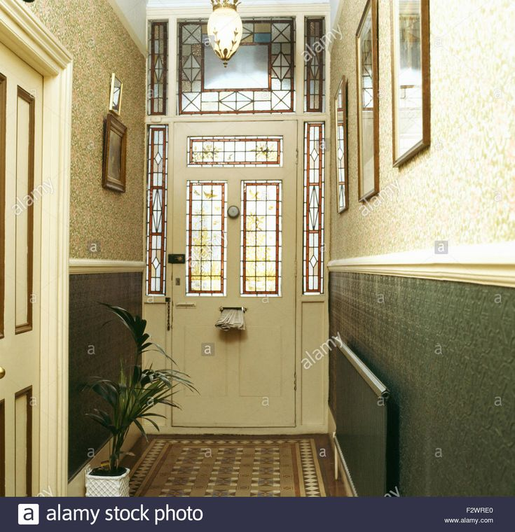Stained glass panels in front door in Victorian style hall with William Morris wallpaper above dado Stock Photo
