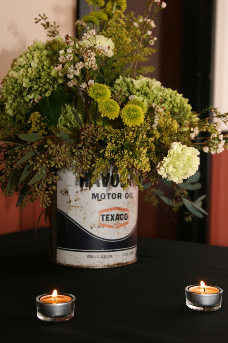 "We had a ""hot rod"" themed wedding we used alot of ""old"" things both automotive and not as decorations. These were 5 quart oil cans from the 50's with a vase inside them as table settings."