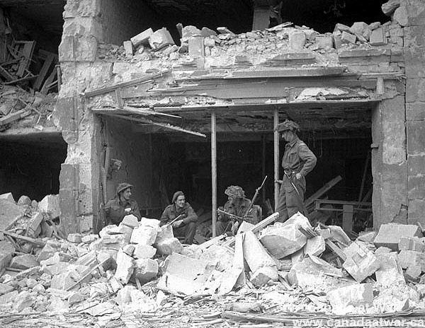 Canadians capture Caen - Personnel of the Regina Rifles inside a damaged building. (L-R): Riflemen Nick Lingor, Bert Colwell, Steven Pelepink, Jimmie Herriott. 10 July 1944, Caen, France.