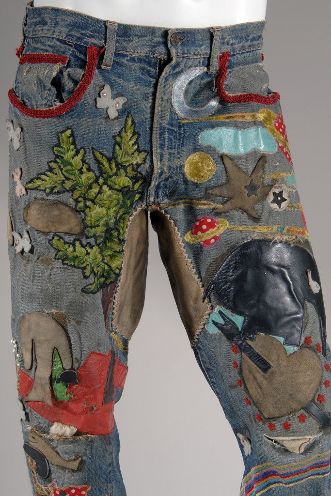 Embellished men's jeans; blue denim 5-pocket jeans with multicolor overall applique, beadwork, hand and machine embroidery, incorporating leather, vinyl, contrast fabric, rhinestones and cord