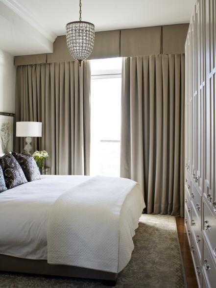 These light wool curtains run floor to ceiling, giving the window in this small bedroom a dramatic and spacious vibe. Custom furniture, including a 10-inch-deep, built-in storage unit, utilizes every foot of space and eliminates the need for bulky dressers. — Kimberley Seldon, designer and owner, Kimberley Seldon Design Group