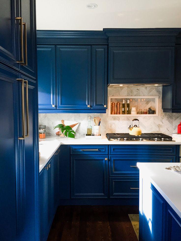 Blue cabinets, gold hardware, marble chevron backsplash