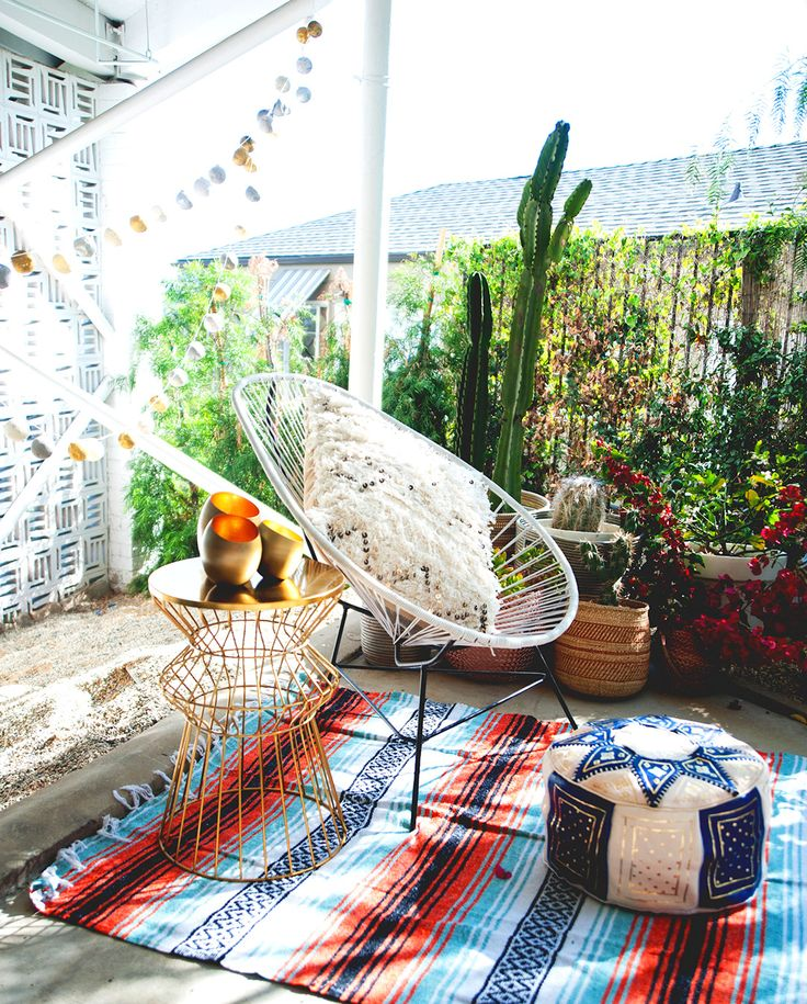 Wire chair, patterned blankets and pillows, string lights, and cactus