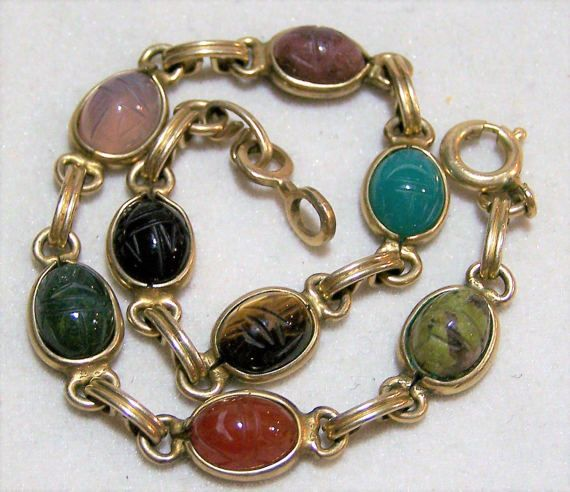 Vintage carved stone 7 scarab bracelet Scarabs include black onyx, tigers eye, chrysoprase, carnelian, chalcedony, rhodonite 12k gold filled Clasp is signed 1/20 12k gf 7 inches long, 3/8 inch wide Each prong set scarab is 10 x 8 mm Good vintage condition, shows no wear International buyers welcome, Over charges are automatically refunded I specialize in vintage scarab jewelry, please visit my scarab jewelry section in my store Priority shipping is optional  Want to see more great b...