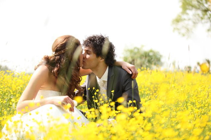 bruidspaar kust in een veld met bloemen