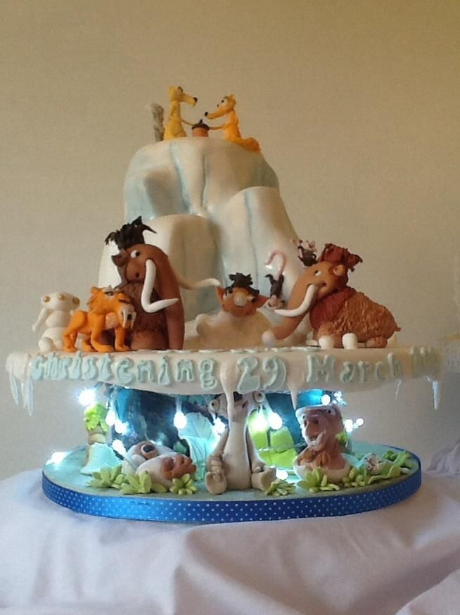 Featuring all key character this two level christening cake takes inspiration from Ice Age land of the Dinosaurs. To highlight underworld LED fairy pigs were included