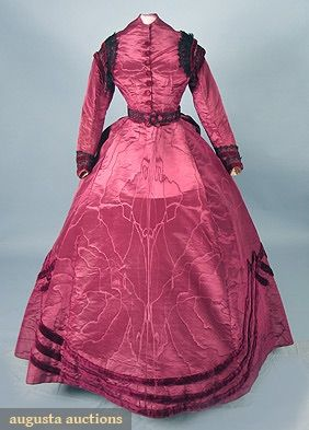 """GARNET SILK TRAINED RECEPTION GOWN, c. 1864  Go Back Lot: 780 April 2006 Vintage Clothing & Textile Auction New Hope, PA 3-piece moire faille trimmed w/ black silk lace & bands of garnet velvet on skirt & sleeve, bodice w/ 7 original velvet covered buttons, all original linings, separate 1.75"""" wide lace trimmed belt, B 36"""", W 25"""", front skirt L 42"""", back skirt L 64"""",t/w black Chantilly lace tippet 17"""" x 152"""", (2 seams on L sleeve unstitched) excellent."""