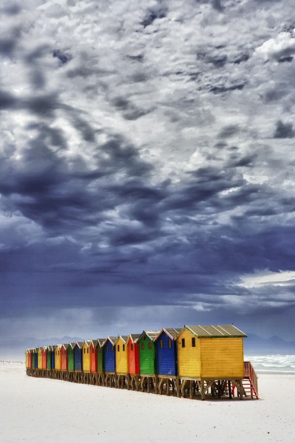 Beach Huts in Muizenberg, Cape Town. Muizenberg is a beach-side suburb of Cape Town, South Africa. It is situated where the shore of the Cape Peninsula curves round to the east on the False Bay coast. It is considered to be the birthplace of surfing in South Africa. Muizenberg has a fine, long beach that in effect stretches all the way round the top of False Bay to the Strand, a distance of over 20 km. False Bay, known for its population of White Sharks.