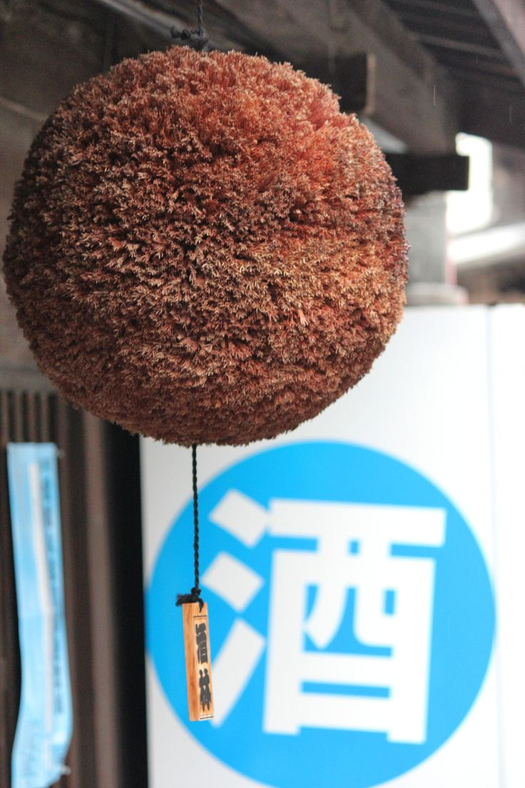 A sugidama ball in front of a sake vending machine advertises that the noble rice beverage is available at this sake store in Dogo.
