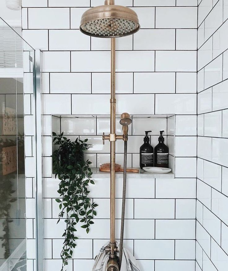 White subway tile shower with brass details