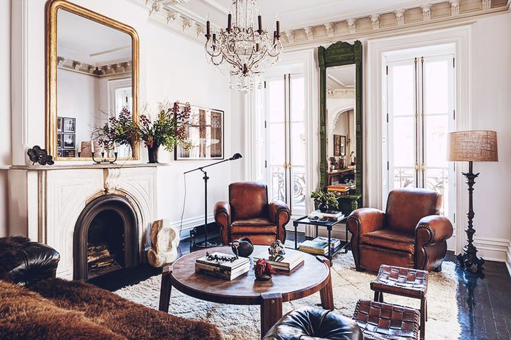 ivory fireplace mantel + oversized brown leather chairs + white walls + wood coffee table + gold mirror