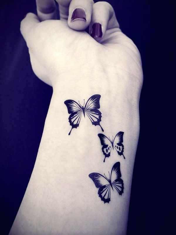 mujer con tatuaje de unas mariposas pequeñas en su antebrazo