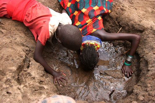 https://flic.kr/p/7XsBvy | CLIMATE CHANGE IN TURKANA | Young girls drink water directly from a shallow hole dug in the sand along River Tarash in Kakuma township in Turkana, April 22nd, 2009. Water is one of the main problems in this region, and the little that is available is shared between human beings and animals. Most rivers in this region have dried up, and only sand is left on riverbeds due to climate change that is affecting the globe. PHOTO/STEPHEN MUDIARI
