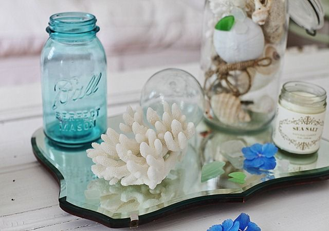 A relaxed atmosphere courtesy of a little coral, canning jar, vintage mirror and shells!
