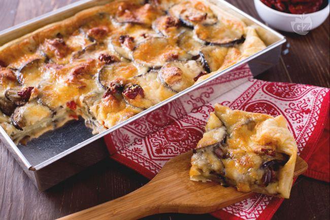 La torta salata di melanzane è una saporita torta rustica di pasta sfoglia farcita con strati di melanzane, pomodori secchi, scamorza e parmigiano.