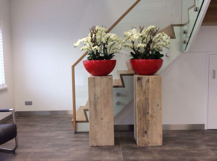 Steigerhout zuilen, verstek gezaagd vormen een rustieke basis voor deze prachtige hoogglans rode schalen met witte orchideeen. De schalen zijn leverbaar in iedere willekeurige RAL of Sikkens verfkleur.