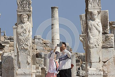Japanese tourists are taking a selfie at the hercules gate in the ancient city of Ephesus Turkey