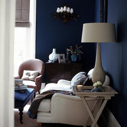 Above: This atmospheric bedroom features walls painted a deep blue shade called Hague from Farrow & Ball.
