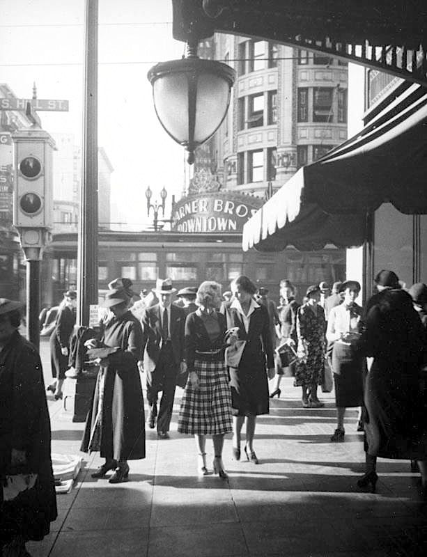 1937 Outside Bullocks department store near the corner of 7th Street and Hill Street in downtown Los Angeles, Ca. USA What I like about this shot are the little details: Everybody is in hats, the semaphore street light, the wonderful light fixture over the sidewalk, the passing street car, and the Warner Bros. Downtown theater. I wonder what was playing there?