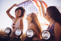 Afro girl flying an American flag with friends stock photo