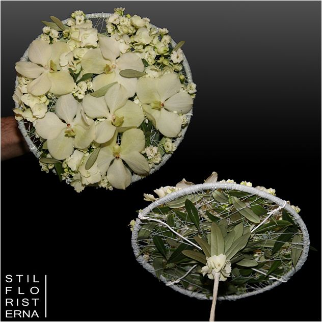 Modern och annorlunda platt brudbukett med vita orkidéer, olivblad och en arbetad undersida med ett tunt skaft.