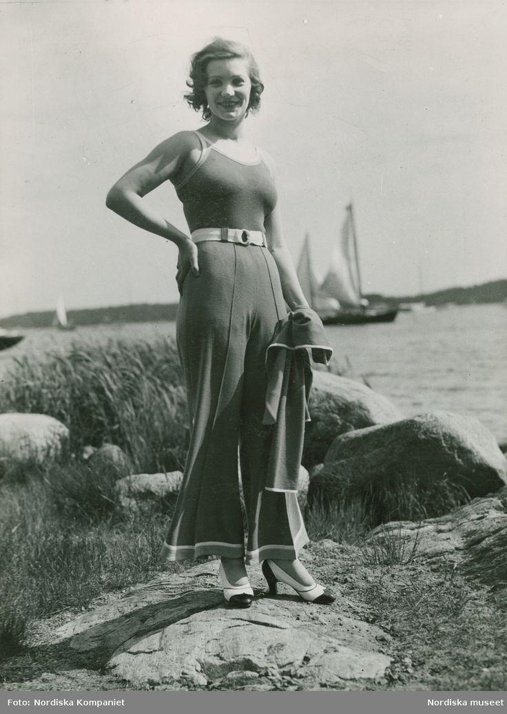 1931. Modell i byxdress och pumps vid Saltsjöbaden, båtar i bakgrunden. Foto: Erik Holmén för Nordiska Kompaniet