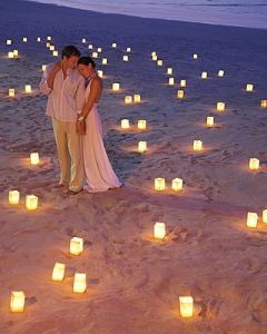 Bride & groom on beach surrounded by candles, unique lighting
