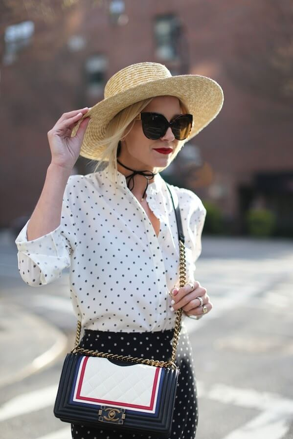A young lady wearing dots print shirt and skirt and statement-making bow choker on the neck