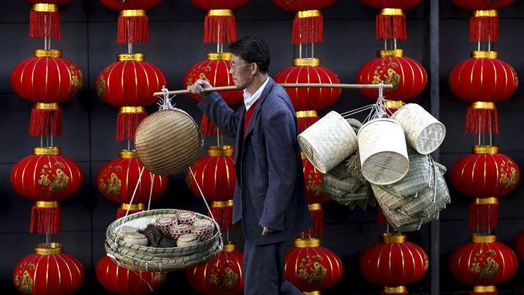 - Vendedor de cestas caminha em frente a lanternas vermelhas colocadas em um shopping de Kunming, na China, para celebrar o Ano Novo. Foto: Stringer / Reuters