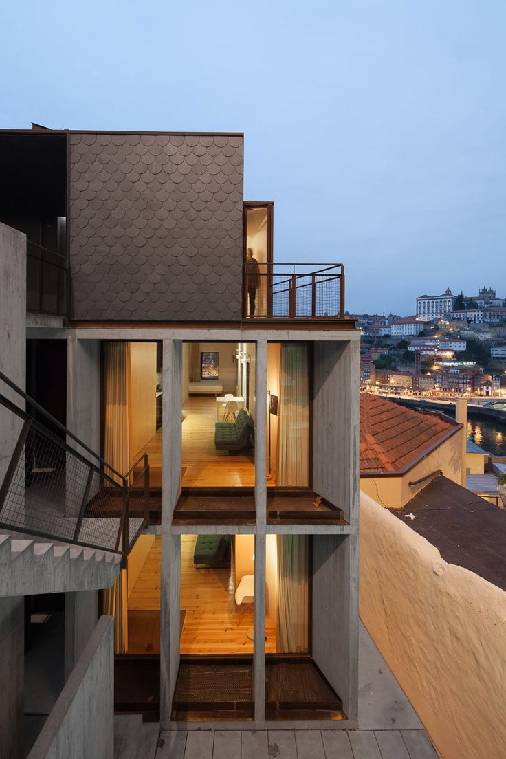 Architects Nuno Melo Sousa and Hugo Ferreira have created a apartment block for holidaymakers in Porto, backing onto a steep granite cliff beside one of the city's most prominent bridges.