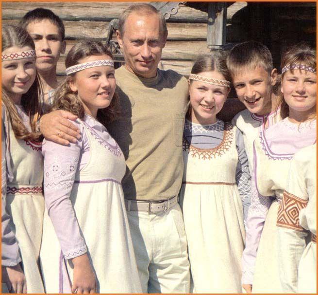 Russia's President Putin posing with  Russian children wearing traditional regional dress.  costume.