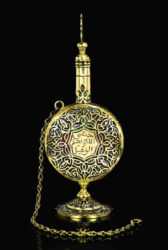 AN ENAMELLED GOLD KOHL BOTTLE, MOROCCO, CIRCA 18TH CENTURY  the round body decorated in a multi-coloured enamel geometric pattern featuring an inscription to the centre to one side, on a short stand set with drop-shaped pink gemstones, the thin elongated neck containing a kohl stick with an enamelled handle and gold chain hooked to body for attaching