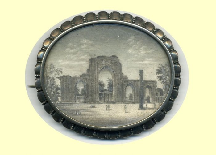 India, The Iron Pillar of Delhi, painted ivory and silver brooch, circa 1850, a view of the Pillar, with figures standing in the foreground, 72 x 60 mm.