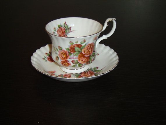 "Centennial Rose pattern circa 1981, pink roses with green leaves, scalloped, gold accenting  The cup is 2 13/16"" (7.1 cm) high x 3 1/2"" (8.9 cm) at the brim and the saucer is 5 1/2"" (14 cm) in diameter  This set is in near mint condition and only appears to have seen use as a collectible  Made of bone china from England by Royal Albert 